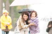 Anne ve çocuk yağmurlu havalarda şemsiye altında. — Stok fotoğraf