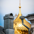 Golden domes with crosses behind old roof. - Stock Photo