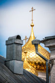 Golden domes with crosses behind old roof. — Stock Photo