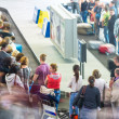 Lots of people getting luggage at airport. - Stock Photo