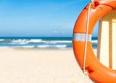 Lifebuoy, mavi gökyüzü ve kumlu plajı ile deniz manzarası. — Stok fotoğraf
