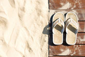 Sand and flip flops on boardwalk at sunny beach. — Stock Photo