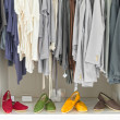 Casual clothes on hangers and shoes at shop. - Stock Photo