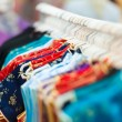 Stockfoto: Rows of colorful clothes on hangers at shop.