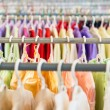 Rows of colorful clothes on hangers at shop. — Stockfoto #22255629
