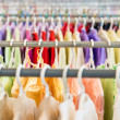 Foto Stock: Rows of colorful clothes on hangers at shop.