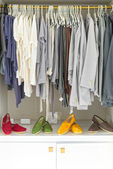 Casual clothes on hangers and shoes at shop. — Stock Photo