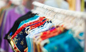 Rows of colorful clothes on hangers at shop. — Foto Stock