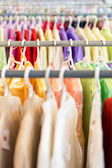 Rows of colorful clothes on hangers at shop. — Stock Photo
