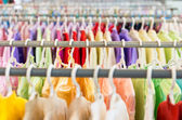 Rows of colorful clothes on hangers at shop. — Zdjęcie stockowe