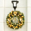 Christmas wreath on lantern on white wall. - Stock Photo