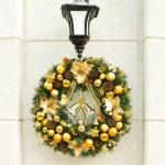 Christmas wreath on lantern on white wall. — Stock Photo