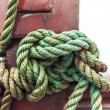 Close-up of rope with tied sea knot on ship deck. - Stock Photo