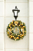 Christmas wreath on lantern on white wall. — Stock Photo