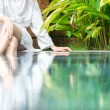 Woman resting at pool with feet in water. - Stock Photo