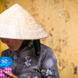 Old poor woman in conical hat holding pink jar. — Stock Photo #22488027