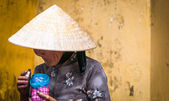 Old poor woman in conical hat holding pink jar. — Stock Photo