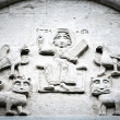Arched wall in church with five carved characters. — Stock Photo