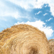 Stock Photo: Haystack outdoors, sky with clouds in background.
