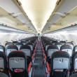 Stockfoto: Vanishing row of black and red seats in airplane.