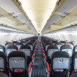 Stock Photo: Vanishing row of black and red seats in airplane.