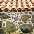 Stock Photo: Tiled roof and wall decorated with stones.