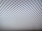 Grijze achtergrond van geperforeerde metalen textuur. — Stockfoto