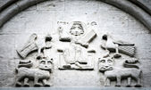 Arched wall in church with five carved characters. — Photo