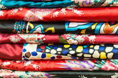 Pile of silk clothes with abstract asian design. — Stock Photo