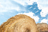 Haystack outdoors, sky with clouds in background. — Stock Photo