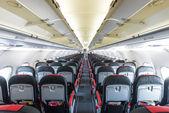 Verdwijnende rij met zwarte en rode zitplaatsen in het vliegtuig. — Stockfoto