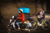 Woman riding scooter at night — Stock Photo