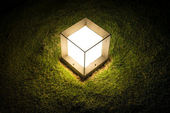 Lighting cube lantern on grass — Stock Photo