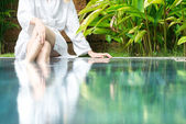 Woman resting at pool with feet in water — Stok fotoğraf