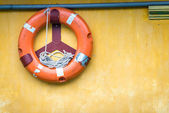 Orange old lifebuoy with rope — Stock Photo