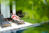 Woman relaxing on chaise longue — Stock Photo