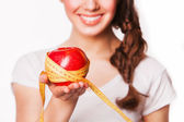 Smiling woman holding an apple and tape measure — Stock Photo