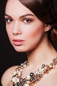 Beautiful woman with perfect makeup wearing jewelry — Stock Photo