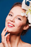 Beautiful smiling woman with a fresh flower lily — Stock Photo