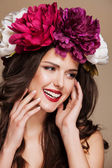 Beautiful smiling woman with bright flowers on her head. touching face — Stock Photo