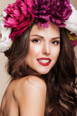 Beautiful happy woman with bright flowers on her head and red lips — Stock Photo