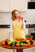 Smiling young woman in the kitchen with vegetables — Stock Photo
