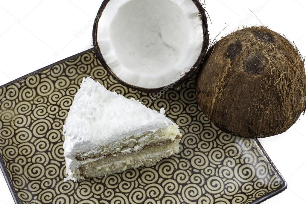 Overhead view of a slice of coconut cake on a plate with a crack coconut next to it.  — Stock Photo #16880093