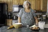 Grandma in a kitchen preparing to bake — Stock Photo