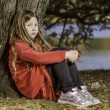 Sad young girl by tree — Stock Photo