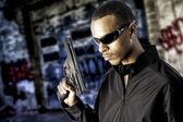 Black male holding a handgun — Stock Photo