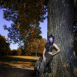 Sexy black gothic woman by tree — Stock Photo