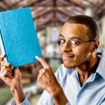 Постер, плакат: Nerdy black male with book