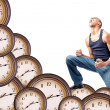 Man kneeling on clocks — Stockfoto
