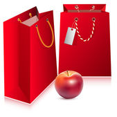 Red bags and ripe red apple. — Stockvector